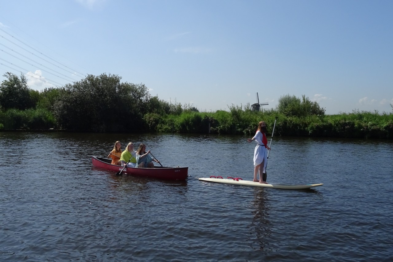 An image taken by Suus' team for the scavenger hunt. Suus, a young person dressed as Jesus in a long white robe and a fake beard, is standing upright on a paddle board holding an oar, in a lake in rural Holland. Behind them is a canoe with three young people dressed as disciples in coloured robes, rowing behind the paddle board.