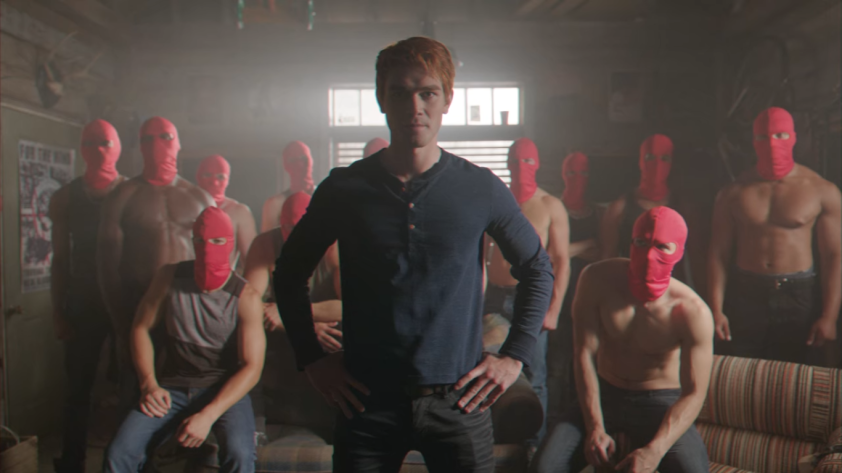 A young man with red hair named Archie Andrews stands in front of eleven buff men, most of whom are shirtless. Apart from Archie, everyone is wearing a red ski mask.