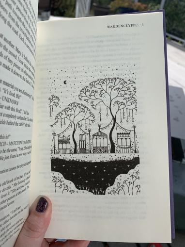An early illustration from Wardenclyffe shows carnival booths, trees, and banners at the Illumination Festival in the town of Valentine. The image is in black and white, with geometric shapes and patterns reminiscent of mandala designs.